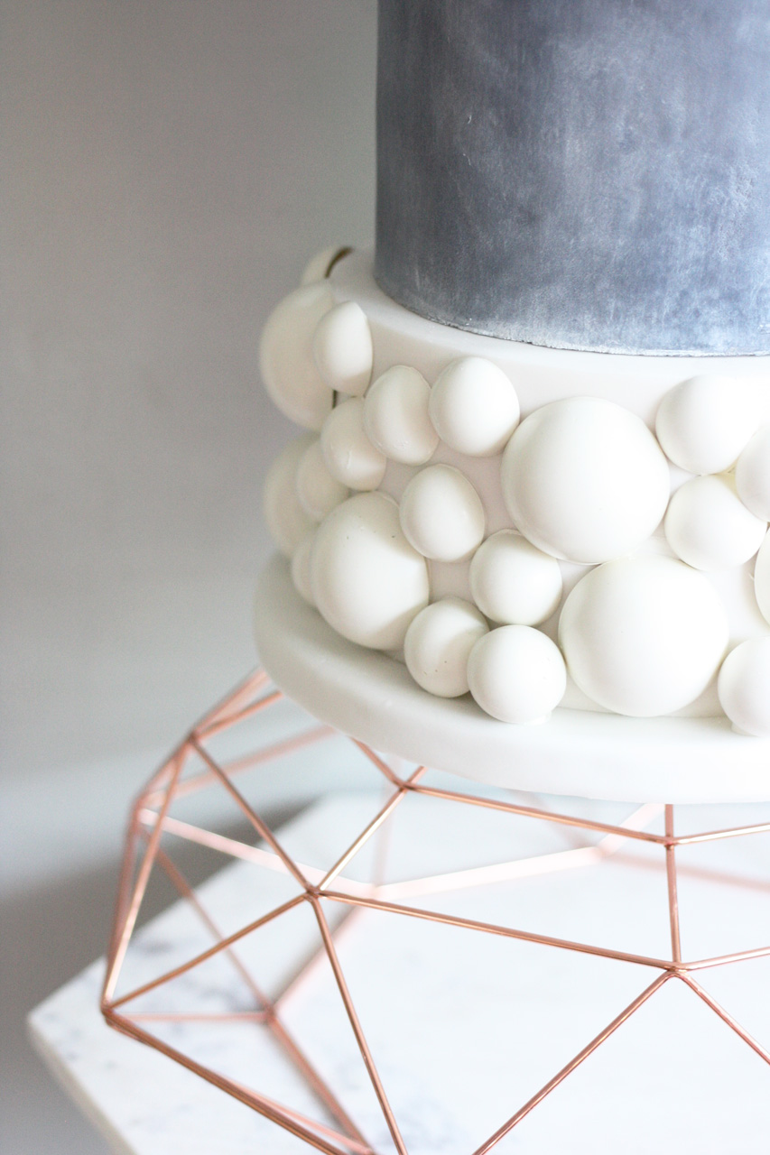 Concrete and white chocolate wedding cake on copper geometric cake stand