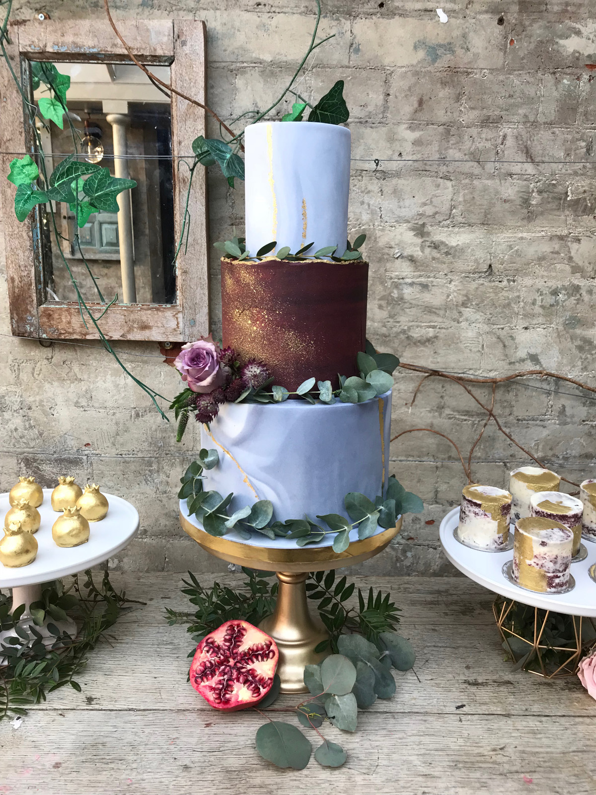 Whimsical marble wedding cake with fondant and buttercream effects and foliage