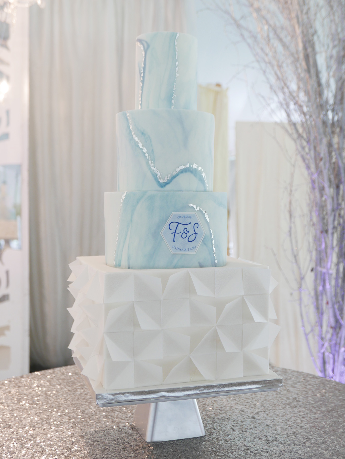 Winter wedding cake with blue marble and wafer paper geometric details