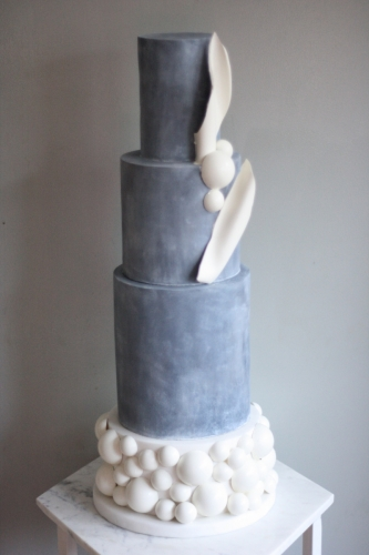 Three tier tall concrete cake with white chocolate balloon spheres and white chocolate shards and twists