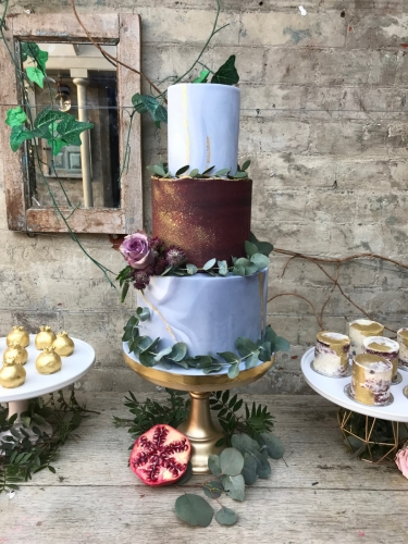 Marble and burgundy wedding cake with dark green foliage and flowers