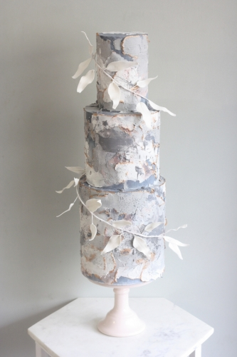 Three tier grey and white textured layer wedding cake with white sugar foliage